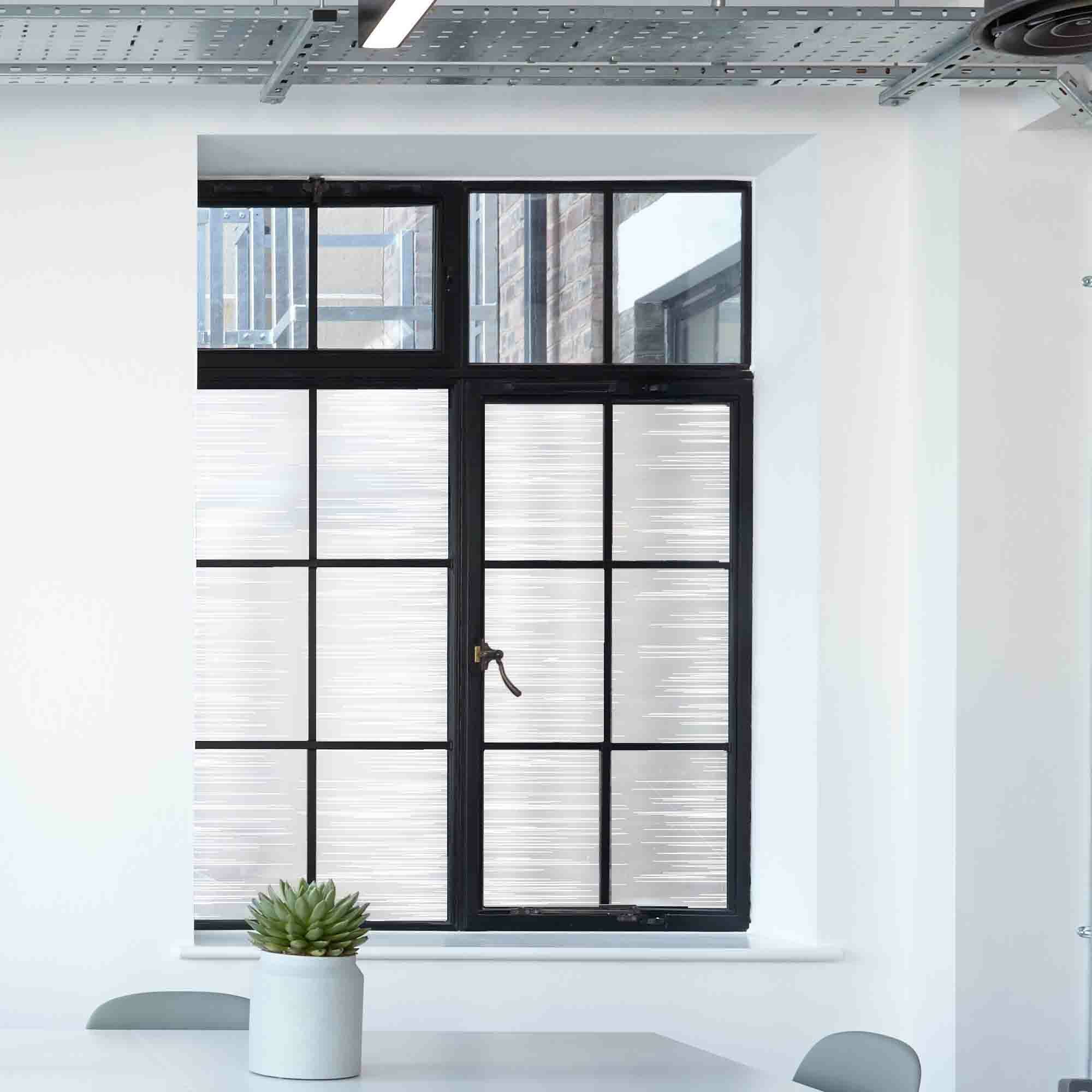 Privacy window film in a contemporary abstract linear pattern shown on multi-paned glass.