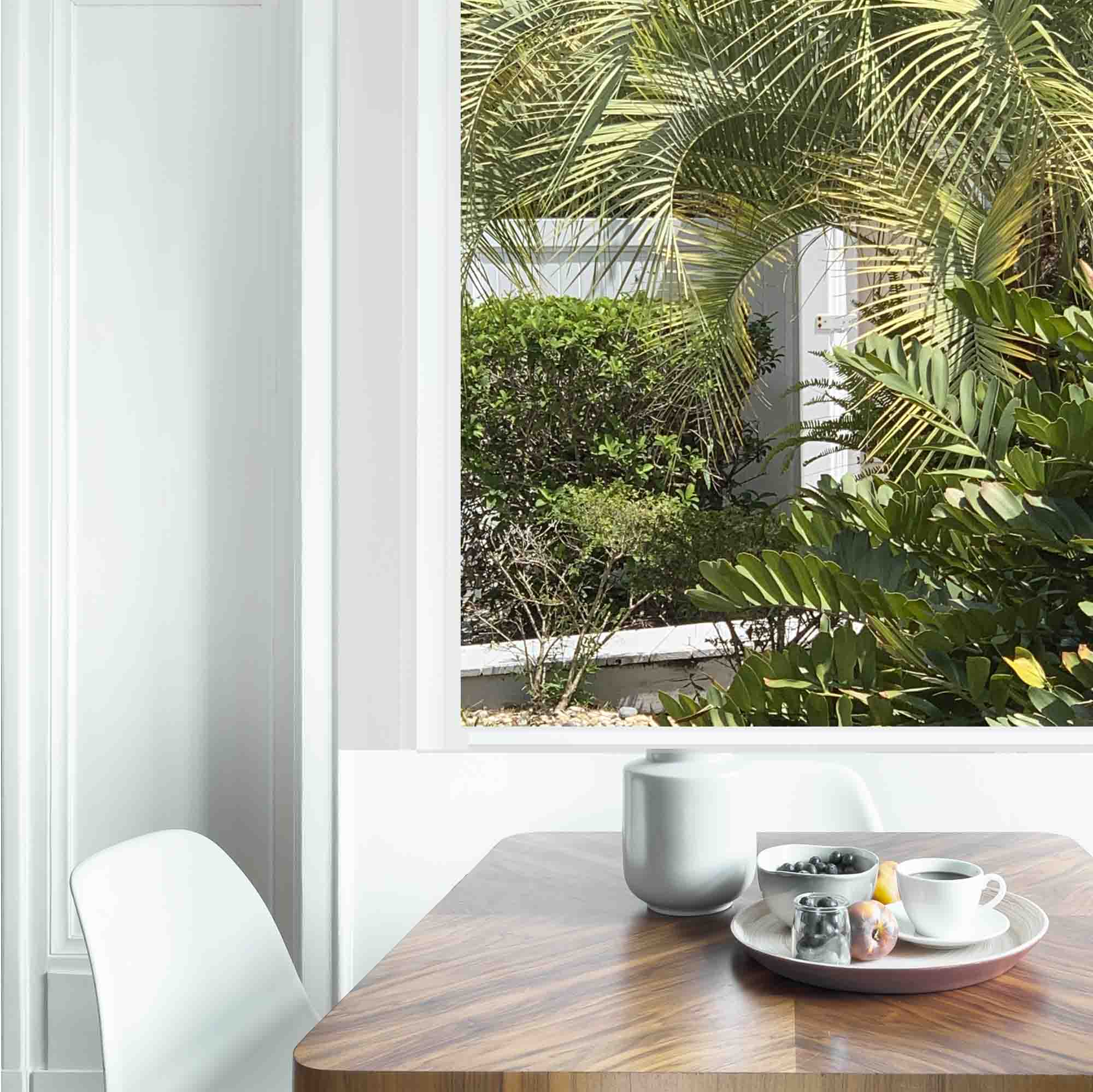 Dining table with fresh flowers and breakfast tray with coffee cup and fruits in real photo of white room interior with empty wall. Paste your painting here