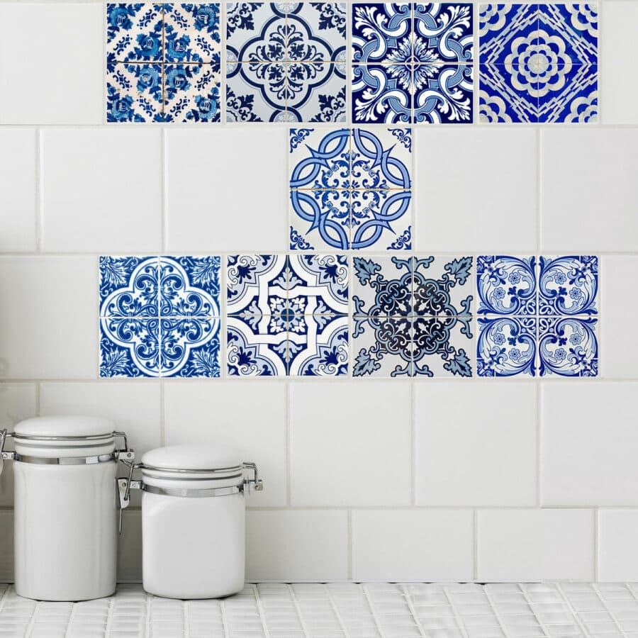 An array of blue and white mosaic tile stickers cover white tiles in a kitchen.