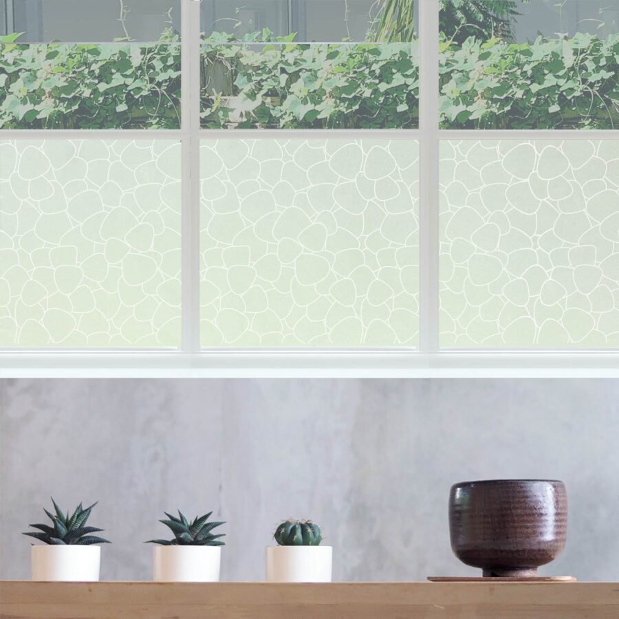 Window privacy film featuring an etched stonework design.