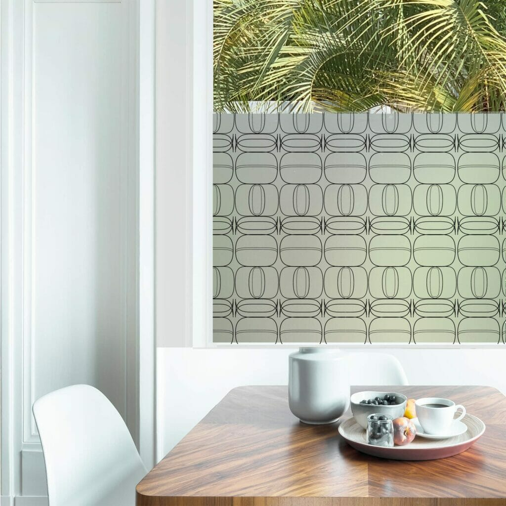 Delicate linear drawings of repetitive oversized jewels adorn a piece of privacy window film in in a family dining room.