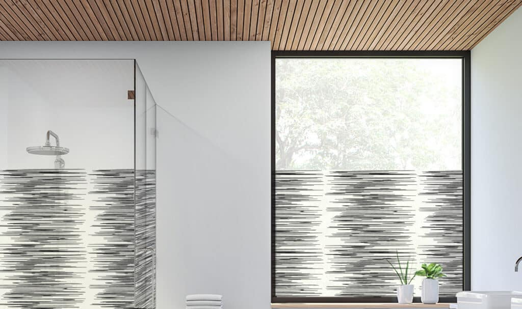 Bathroom window film is featured on a shower door and window. The privacy film is covered in a linear horizontal lined pattern.