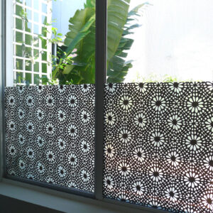 Window privacy film adorns the bottom half of a window. The pattern features an all-over print of small a symmetric petals and flower centers.