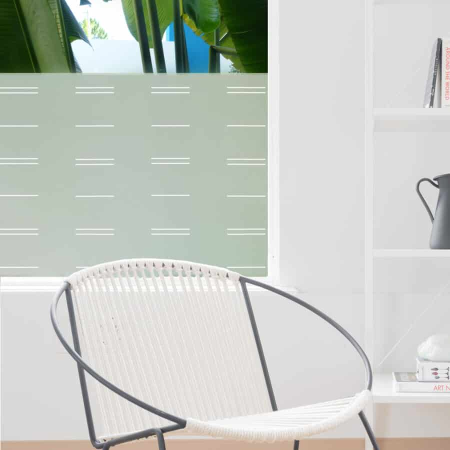 White contemporary horizontal lines cover a piece of decorative window privacy film on a bathroom door.